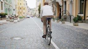 Metragem do movimento lento do homem novo que comuta para trabalhar na bicicleta do esporte do vintage vídeos de arquivo