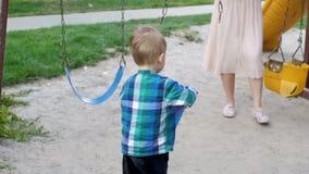 Metragem do movimento lento do menino descalço da criança que leva a cubeta e a pá plásticas na caixa de areia no parque vídeos de arquivo