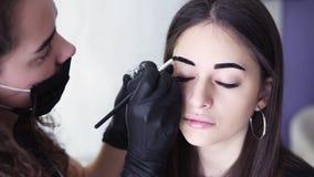 A metragem do ombro, esteticista caucasiano está aplicando a pintura escura nas testas da jovem mulher pela tintura marrom, color video estoque