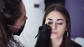 A metragem do ombro, esteticista caucasiano está aplicando a pintura escura nas testas da jovem mulher pela tintura marrom, color vídeos de arquivo