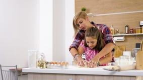 A metragem do slider 4K da zorra da filha amassa a massa na cozinha video estoque