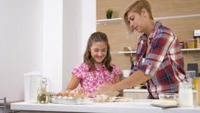Metragem do slider 4K da zorra da mãe e do cozimento novo da filha e do cozimento junto na cozinha video estoque