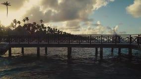 Metragem do zangão do molhe de madeira do cais sobre a lagoa, das palmas na praia e do fundo do céu nebuloso, noite, por do sol filme