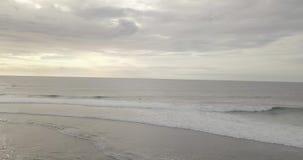 Metragem do zang?o do nascer do sol de um penhasco e de uma praia calmos perto do templo de Uluwatu, Bali, Indon?sia filme