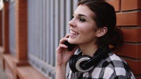 Metragem extremamente próxima Aturdir, moça está falando no telefone celular com amigo Parte externa ereta que inclina-se na video estoque