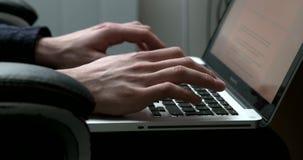 Metragem handheld da vista lateral de um homem que datilografa em um portátil vídeos de arquivo