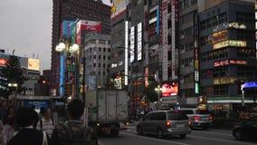 Metragem Handheld de uma rua do centro ocupada do Tóquio na noite Os sinais de néon piscam nas construções altas e o tráfego e os filme