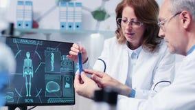 Metragem handheld do close-up do pesquisador fêmea e masculino que debate sobre um tubo com amostra azul video estoque