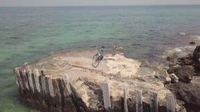 Metragem 4k aérea de um bycicle no cais concreto velho pelo mar no verão filme