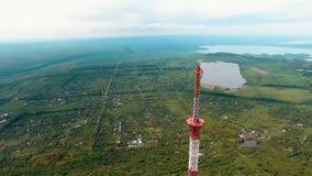 Metragem 4k aérea do voo do zangão em torno da torre de rádio da tevê da telecomunicação no subúrbio de Stavropol Rússia filme