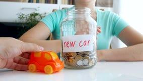 Metragem 4k conceptual do dinheiro da economia da jovem mulher para o carro novo Equitação do carro do brinquedo na tabela video estoque