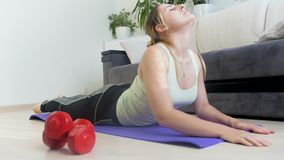 metragem 4k da jovem mulher que estica na esteira da ioga em casa após ter feito exercícios da aptidão video estoque
