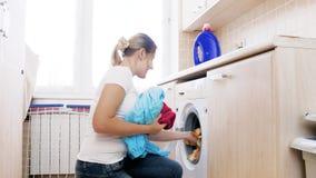 metragem 4k da máquina de lavar bonita nova da carga da dona de casa com roupa suja filme