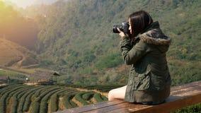 metragem 4K da mulher asiática feliz do turista que toma a foto da natureza bonita da plantação do campo do chá em Ásia pela câma vídeos de arquivo