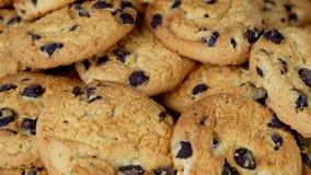 metragem 4K de cookies caseiros dos pedaços de chocolate no fundo de madeira do marrom escuro, girando vídeos de arquivo