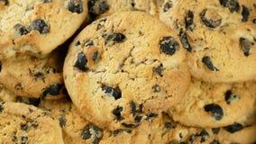 metragem 4K de cookies caseiros dos pedaços de chocolate no fundo de madeira do marrom escuro, girando filme