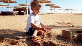metragem 4k de pouco menino da criança que joga com a areia molhada na praia do mar vídeos de arquivo