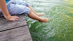 metragem 4k de pouco menino da criança que senta-se no riverbank e que espirra a água com seus pés Criança que mergulha os pés no video estoque