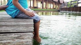 metragem 4k de pouco menino da crian?a que senta-se no riverbank e que espirra a ?gua com seus p?s Crian?a que mergulha os p?s no filme