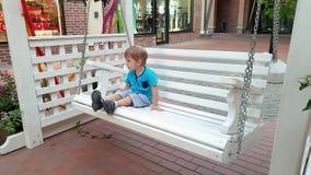 metragem 4k do assento do menino da criança no balanço do banco na rua da cidade video estoque