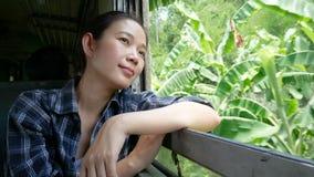 a metragem 4K do curso asiático da mulher pelo trem que olha fora de uma janela do trem no começo railway do trem em Banguecoque  vídeos de arquivo