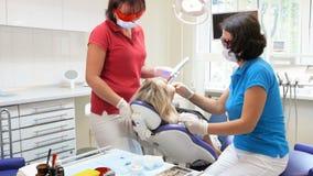 metragem 4k do dentista e do assistente que tratam os dentes pacientes do ` s com a cura do photopolymer filme