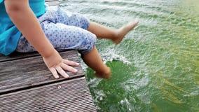 metragem 4k do menino adorável da criança que senta-se no riverbank e que mergulha seus pés na água Pés moventes da criança e vídeos de arquivo