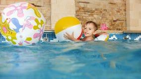 metragem 4k do rapaz pequeno de sorriso feliz que joga com as bolas de praia coloridas infláveis na piscina vídeos de arquivo