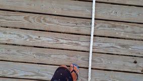 metragem 4k dos pés masculinos nos falhanços de aleta que andam na passagem de madeira no cais longo no mar vídeos de arquivo