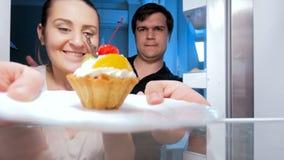 metragem 4k dos pares novos que lutam pelo bolo no refrigerador na cozinha vídeos de arquivo
