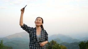 metragem 4k a mulher asiática bonita que tem o bate-papo video usando o smartphone que compartilha fora da opinião da natureza do filme