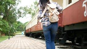 metragem 4k A mulher asiática do turista na estação de trem, leva a trouxa e para andar ao trem curso em Ásia pelo trem do vintag filme