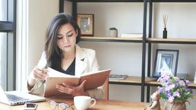 a metragem 4K, a mulher de negócio asiática bonita que sentam-se com leitura do portátil do computador e a aleta sobre o livro de vídeos de arquivo