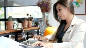 metragem 4K, mulher de negócio ocupada que trabalham com laptop e calculadora no café da cafetaria na cidade na manhã vídeos de arquivo