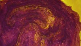 metragem 4k Tinta na água Tinta violeta e amarela que reage na água que cria o fundo abstrato vídeos de arquivo
