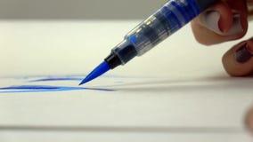 metragem Lento-mo A mão da menina do artista tira uma escova da aquarela com tinta azul Close-up vídeos de arquivo