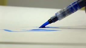metragem Lento-mo A mão da menina do artista tira uma escova da aquarela com tinta azul Close-up filme