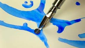 metragem Lento-mo A mão da menina do artista tira uma pena com tinta azul Close-up vídeos de arquivo