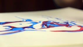 metragem Lento-mo A mão da menina do artista tira uma pena com tinta vermelha Close-up filme