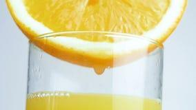 Metragem macro do close up da gota que goteja lentamente do lado da laranja no vidro do suco video estoque