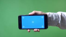 Metragem próxima da mão do ` s do homem que aponta o telefone com chromakey in camera, fundo do chromakey video estoque
