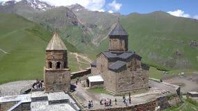 Metragem rápida espetacular aérea à igreja de trindade de Gergeti perto da vila Gergeti em Geórgia, sob a montagem Kazbegi filme
