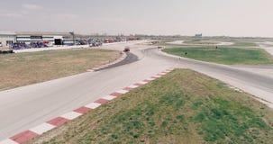A metragem a?rea da trilha de corridas de carros com o campeonato dos cantos que conduz o asfalto cinem?tico do olhar queimou o d filme
