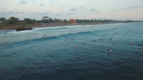 Metraggio aereo dei surfisti in oceano che aspetta grande Wave nella sera stock footage