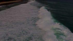 Metraggio aereo del fuco delle onde di oceano che si rompono prima della riva sul tramonto Bali, Indonesia archivi video