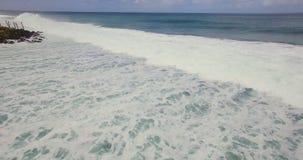 Metraggio aereo del fuco 4k delle onde di oceano che si rompono prima della riva Bali, Indonesia archivi video