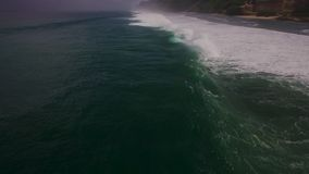 Metraggio aereo del movimento lento del fuco delle onde di oceano che si rompono prima della riva Bali, Indonesia video d archivio