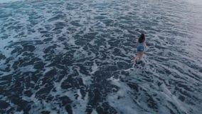 Metraggio aereo della spiaggia nera dell'oceano al tramonto su Bali con la bella ragazza, vista meravigliosa archivi video