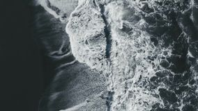 Metraggio aereo delle onde che si rompono contro la spiaggia di sabbia nera in Vik Iceland stock footage