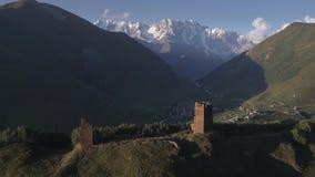 Metraggio aereo delle torri antiche di Svaneti con un villaggio nella valle video d archivio